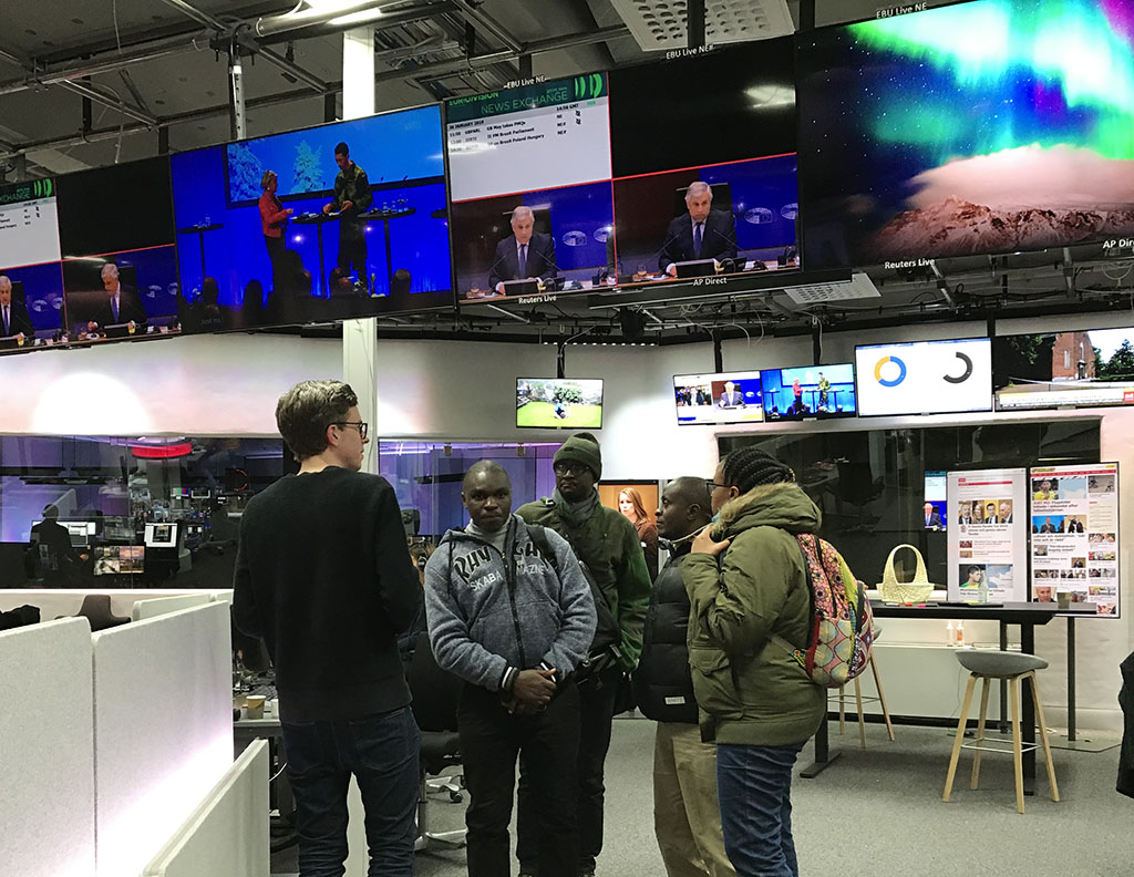 Group of persons in the middle of a TV newsroom. Big screens above heads showing images of news broadcasts. Desks and computers in the background.