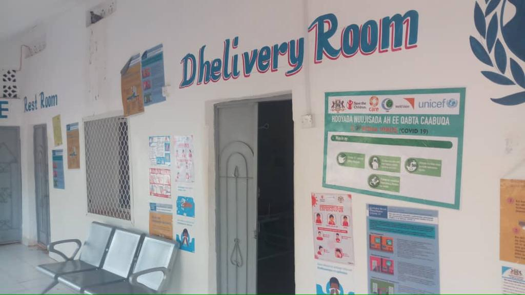 Delivery room painted over doorway of a white building information posters on the wall to the right of the doorway, sofa on the left hand side